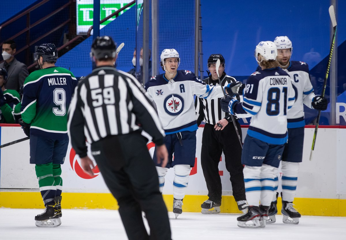 Winnipeg Jets' Mark Scheifele, back centre, Kyle Connor (81) and Blake Wheeler (26) celebrate Scheifele's goal as Vancouver Canucks' J.T. Miller (9) skates to the bench during the first period of an NHL hockey game in Vancouver, on Friday, February 19, 2021. THE CANADIAN PRESS/Darryl Dyck