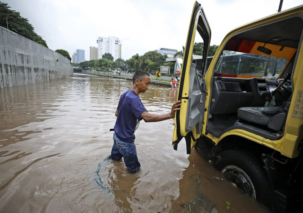 A man steps out of his truck after it was stuck on a flooded toll road following heavy rains in Jakarta, Indonesia, Saturday, Feb. 20, 2021. Heavy downpours combined with poor city sewage planning often causes heavy flooding in parts of greater Jakarta. (AP Photo/Dita Alangkara).