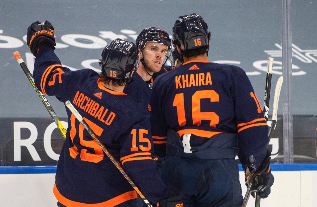 Edmonton Oilers' Josh Archibald (15), Connor McDavid (97), and Jujhar Khaira (16) celebrate a goal against the Calgary Flames during second period NHL action in Edmonton on Saturday, February 20, 2021. THE CANADIAN PRESS/Jason Franson.