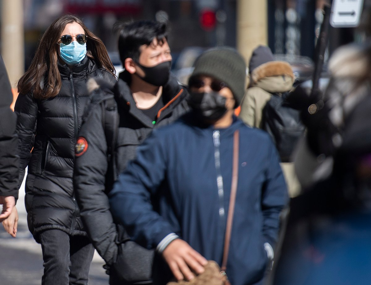 People wear face masks as they walk along a street in Montreal, Sunday, February 21, 2021, as the COVID-19 pandemic continues in Canada and around the world.