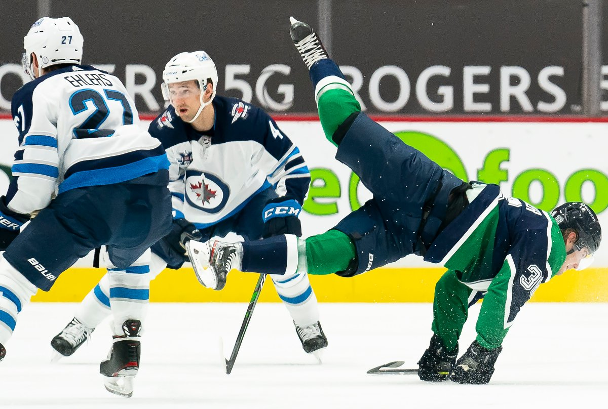 Vancouver Canucks left wing Nils Hoglander (36) fights for control of the puck with Winnipeg Jets defenceman Neal Pionk (4) during first period NHL action in Vancouver, Sunday, February 21, 2021.