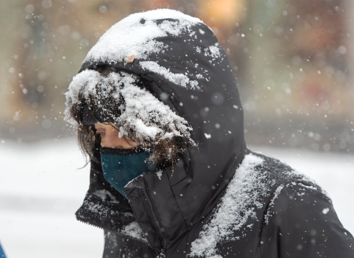 A pedestrian bundles up against the snow and COVID-19 in downtown Montreal, Monday, February 22, 2021.