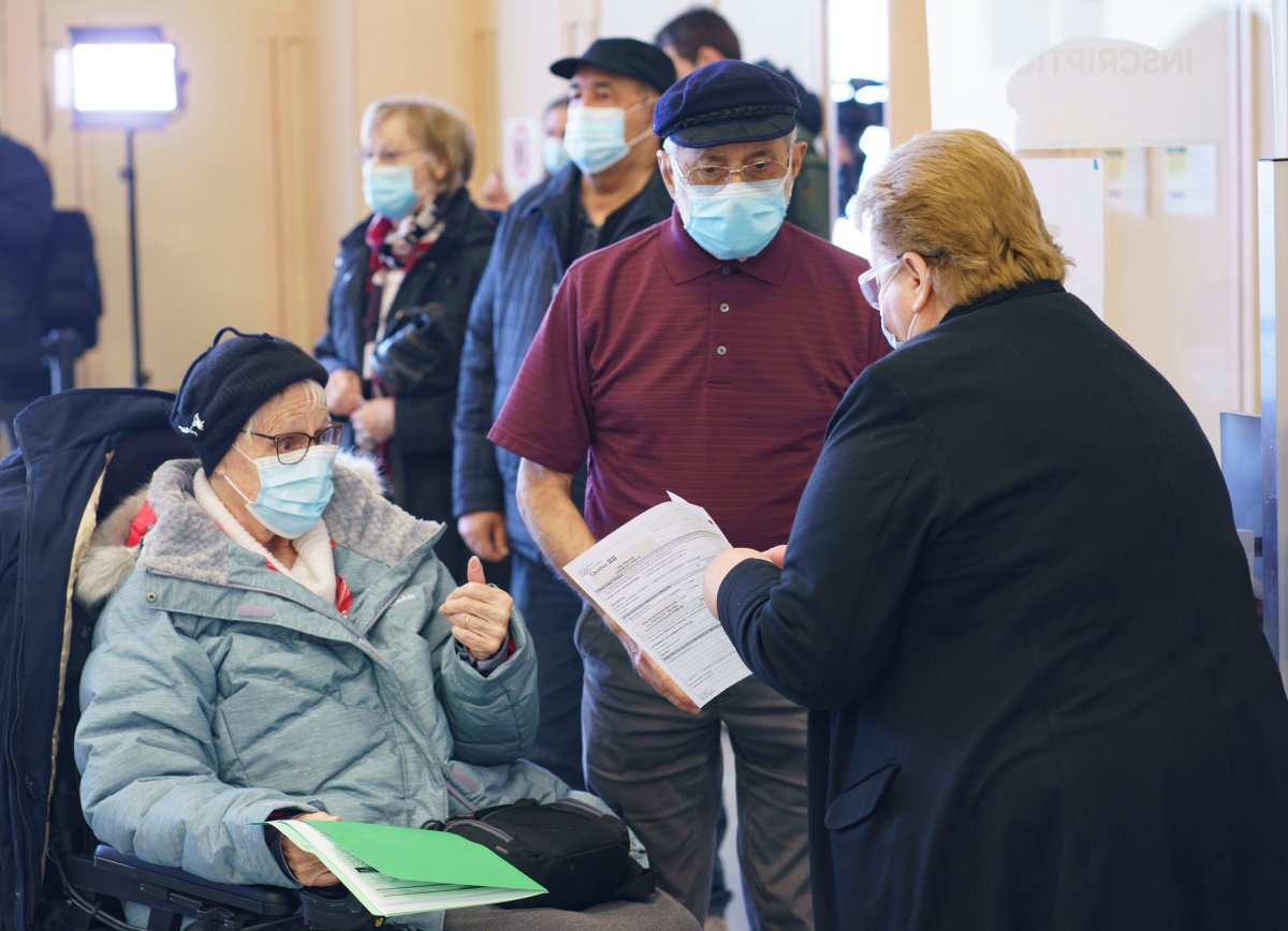People register to receive their first dose of COVID-19 vaccination in Laval, Que., on Thursday, Feb. 25, 2021, marking the start of mass vaccination in the province of Quebec.