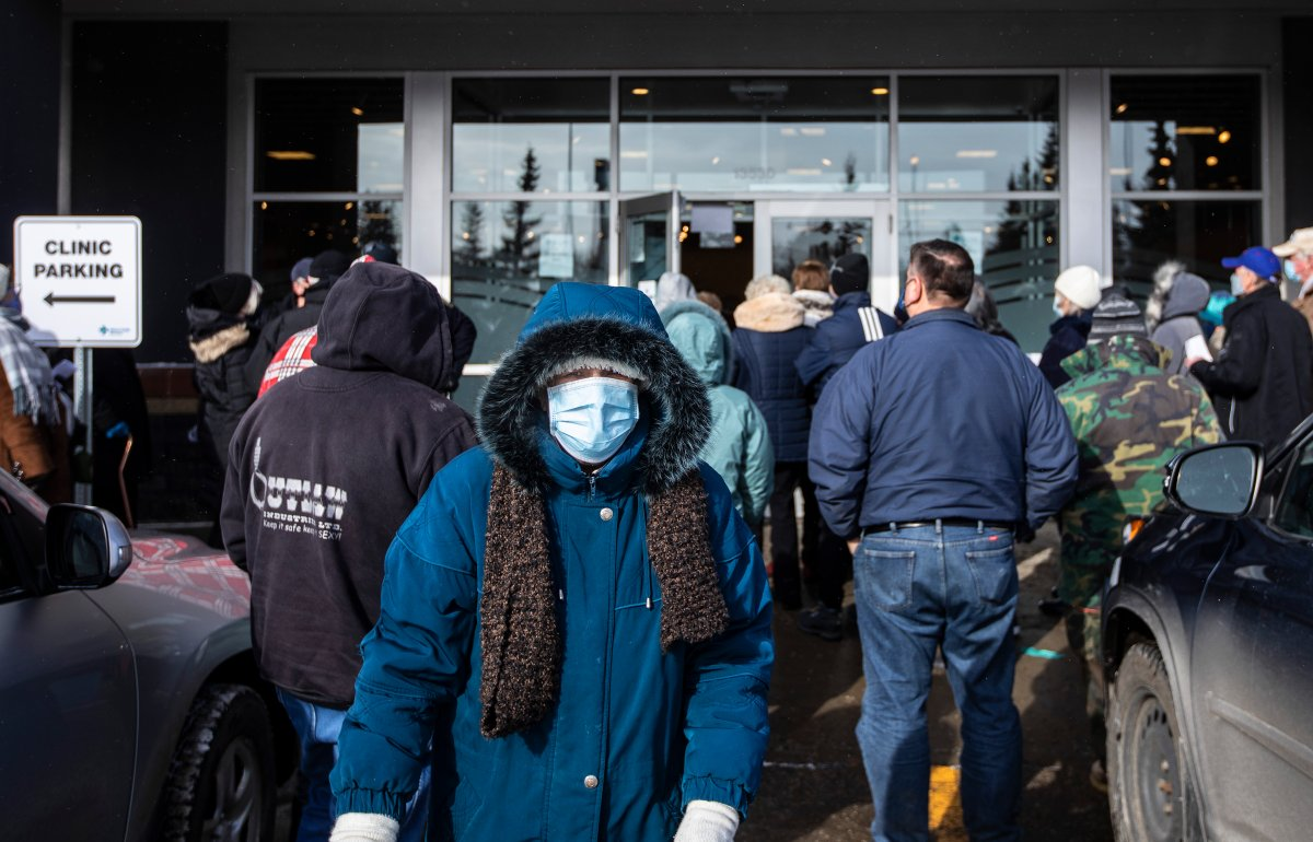 People line up outside a vaccine clinic as seniors wait to get the COVID-19 vaccine in Edmonton, Alta., on Friday, Feb. 26, 2021.