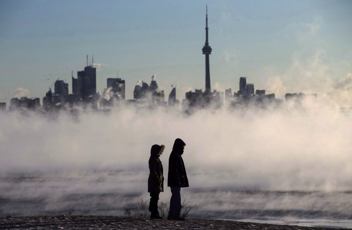 Steam rises as people look out on Lake Ontario in front of the skyline during extreme cold weather in Toronto on Saturday, Feb. 13, 2016.