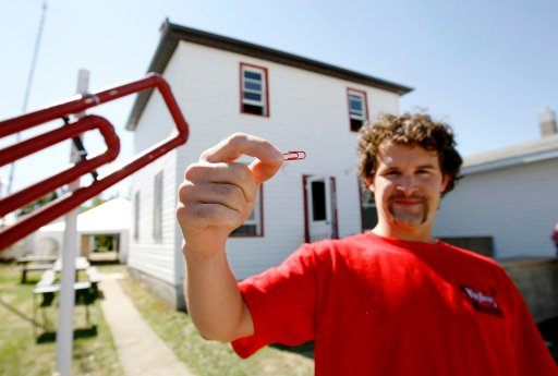 Kyle MacDonald holds up a red paper clip in front of his house in Kipling, Sask. on Friday, Sept. 1, 2006. The small Saskatchewan farming town is rolling out the red carpet for a weekend-long house-warming party for Kyle MacDonald, who traded up from a red paper clip all the way up to a house. (CP PHOTO/Troy Fleece)