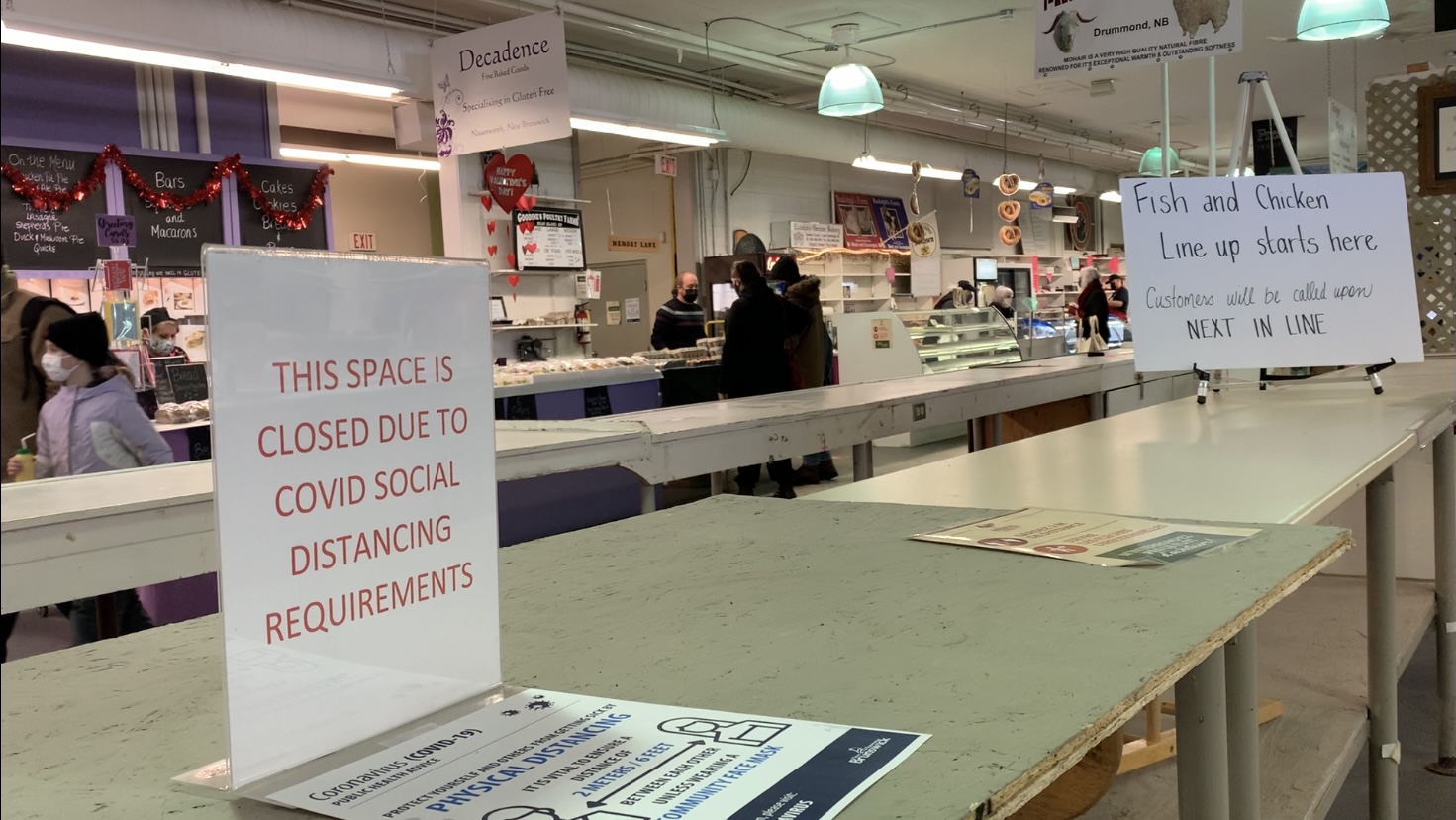 A sign inside The Fredericton Boyce Farmers Market explains why the middle isle is lacking vendors