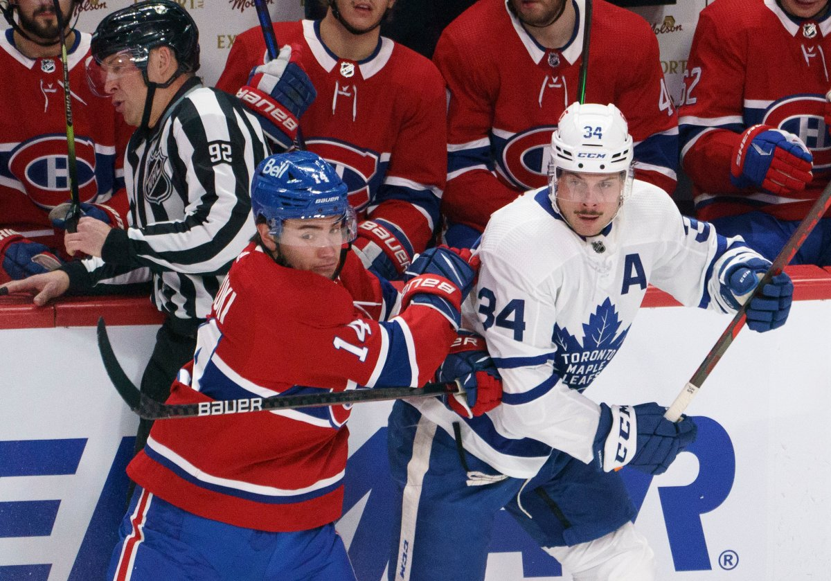 Montreal Canadiens' Nick Suzuki fends off Toronto Maple Leafs' Auston Matthews during second period NHL hockey action in Montreal on Wednesday, February 10, 2021.