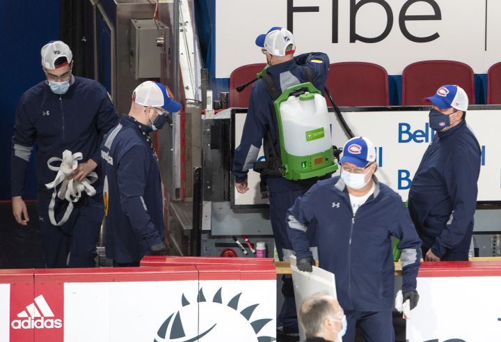 Arena workers clean the player's bench before NHL hockey action between the Edmonton Oilers and Montreal Canadiens, in Montreal, Thursday, Feb. 11, 2021. The game has been delayed by an hour after an Oilers player was placed on the league's COVID-19 protocol.