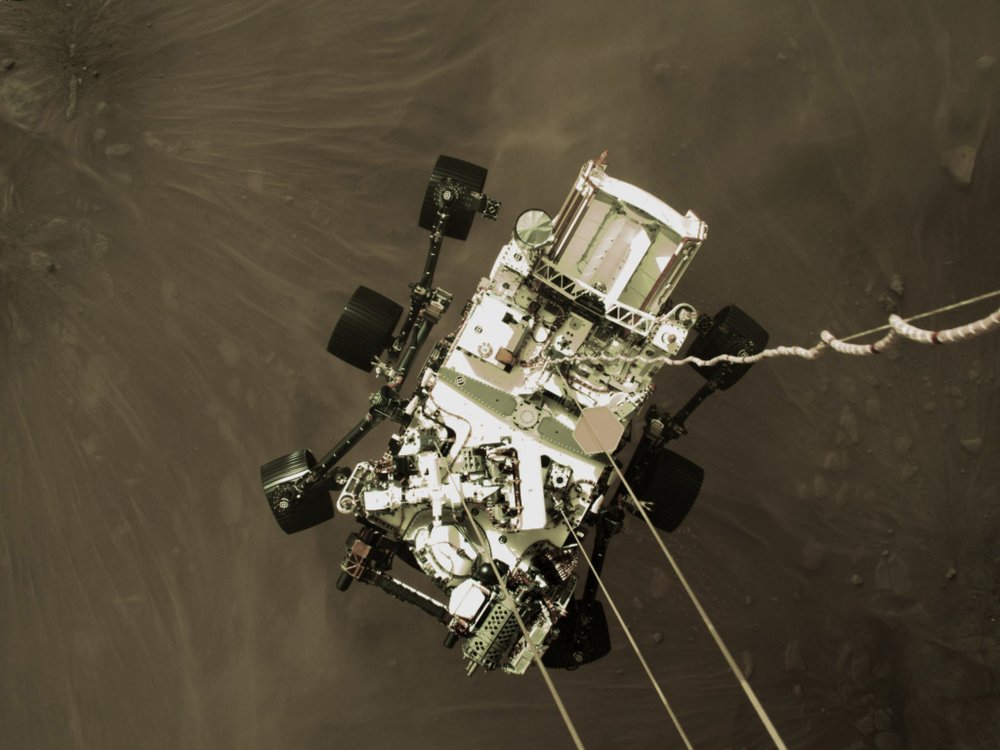 Photo provided by NASA shows the Perseverance rover lowered towards the surface of Mars during its powered descent. (NASA via AP).