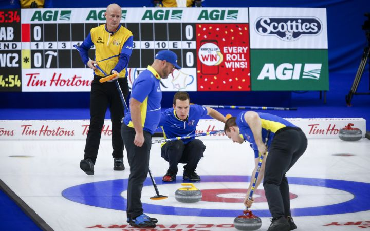 Team Alberta skip Brendan Bottcher, centre, directs his teammates as Team Wild Card Two skip Kevin Koe, left, looks on during the Brier curling final in Calgary, Alta., Sunday, March 14, 2021.