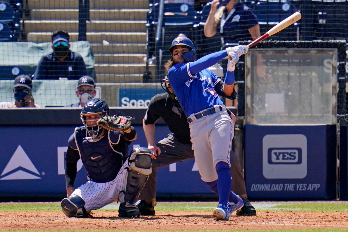 The Toronto Blue Jays' Bo Bichette, right, watches his solo home run off New York Yankees pitcher Luis Cessa during the fifth inning of a spring training exhibition baseball game in Tampa, Fla., Wednesday, March 24, 2021.