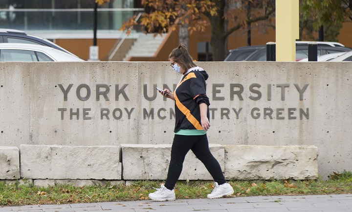 A student wearing a face mask walks at York University in Toronto, Canada, on Oct. 20, 2020.