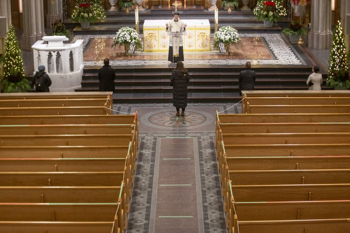 Father Ed Curtis performs Holy Communion services at St. Michael's Cathedral Basilica, in Toronto, Thursday, Dec. 24, 2020.