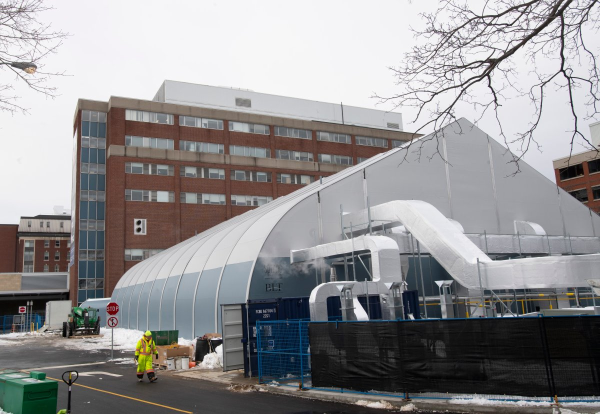A worker walks past a temporary structure under construction outside the civic campus of the Ottawa Hospital Wednesday, January 6, 2021 in Ottawa. Ottawa Public Health says 95 per cent of acute card beds are currently occupied across the city's health-care system as of Tuesday, March 30, 2021.