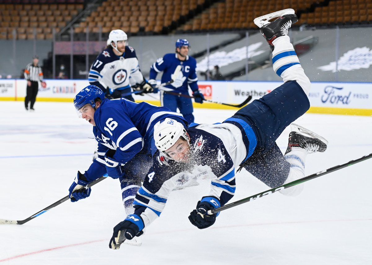 Toronto Maple Leafs right wing Mitchell Marner (16) scores on an empty net and take a hit from Winnipeg Jets defenceman Neal Pionk (4) during third-period NHL hockey action in Toronto on Monday, Jan. 18, 2021.