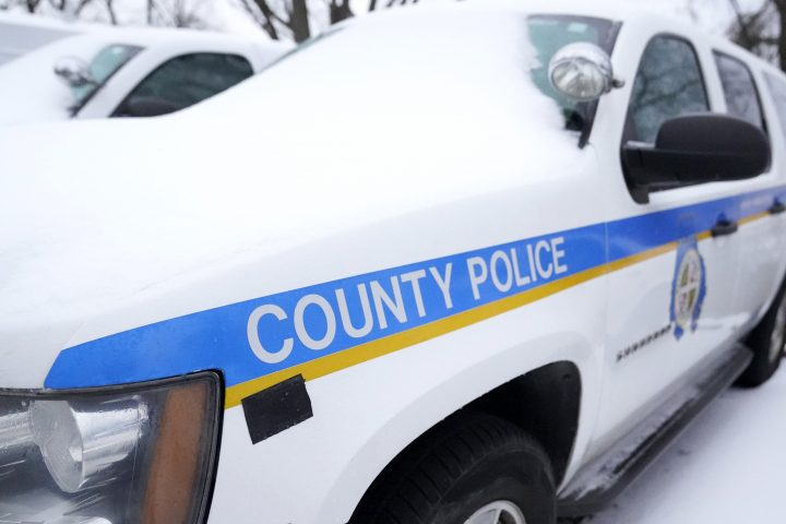 A Baltimore County police SUV is seen covered with snow while parked in a lot, Thursday, Feb. 18, 2021, in Hunt Valley, Md.