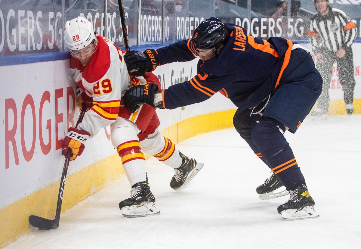 Edmonton Oilers' Adam Larsson (6) checks Calgary Flames' Dillon Dube (29) during first period NHL action in Edmonton on Saturday, February 20, 2021. THE CANADIAN PRESS/Jason Franson.