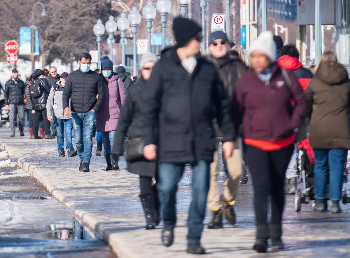 People wear face masks as they walk in the Old Port in Montreal, Sunday, Feb. 28, 2021, as the COVID-19 pandemic continues in Canada and around the world.