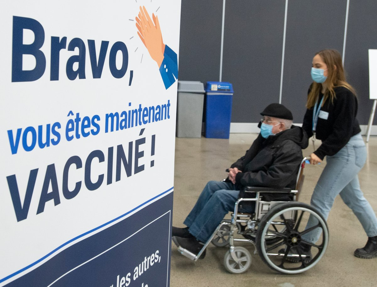 Seniors pass a congratulatory sign after receiving their COVID-19 vaccinations at the Palais de Congress site as Quebec begins mass vaccinations based on age across the province, Monday, March 1, 2021 in Montreal.
