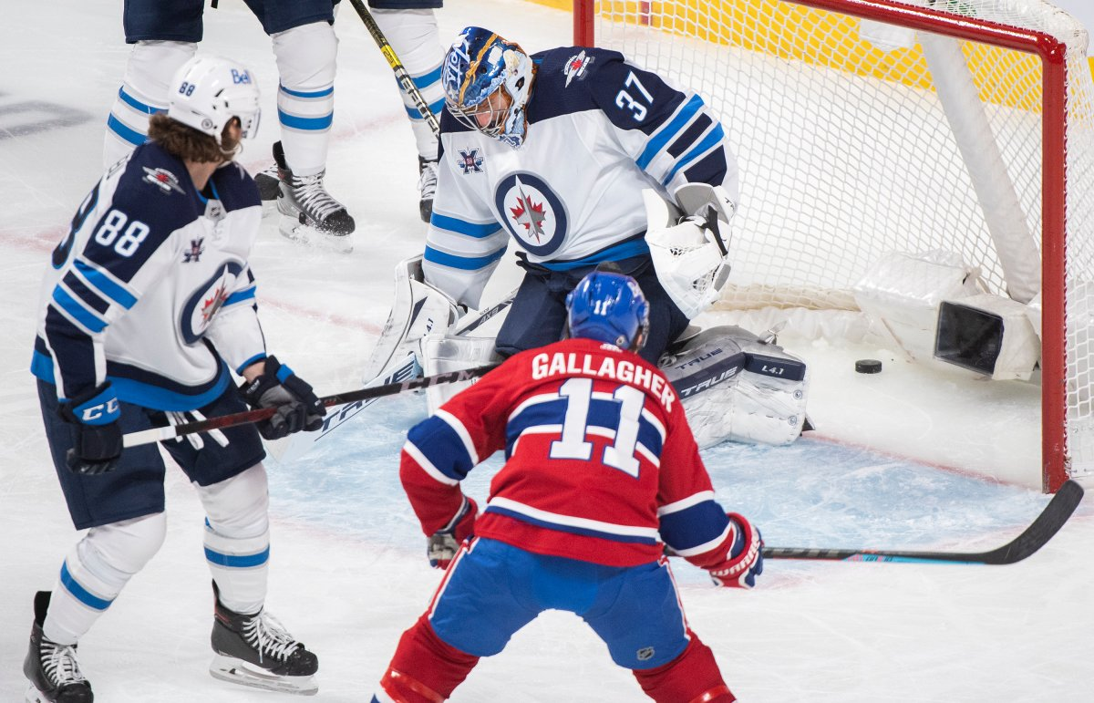 Montreal Canadiens' Brendan Gallagher (11) scores against Winnipeg Jets goaltender Connor Hellebuyck as Jets' Nathan Beaulieu (88) defends during second period NHL hockey action in Montreal, Saturday, March 6, 2021.