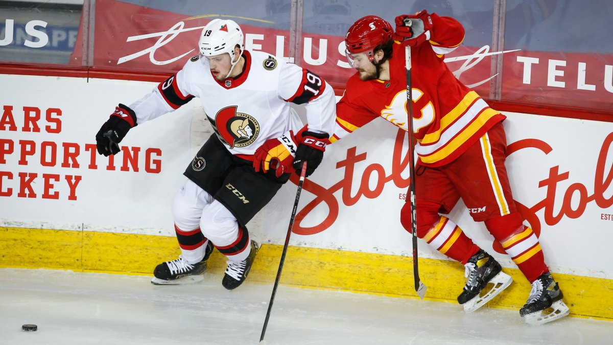 Ottawa Senators' Drake Batherson, left, and Calgary Flames' Rasmus Andersson chase the puck during second period NHL hockey action in Calgary, Sunday, March 7, 2021.