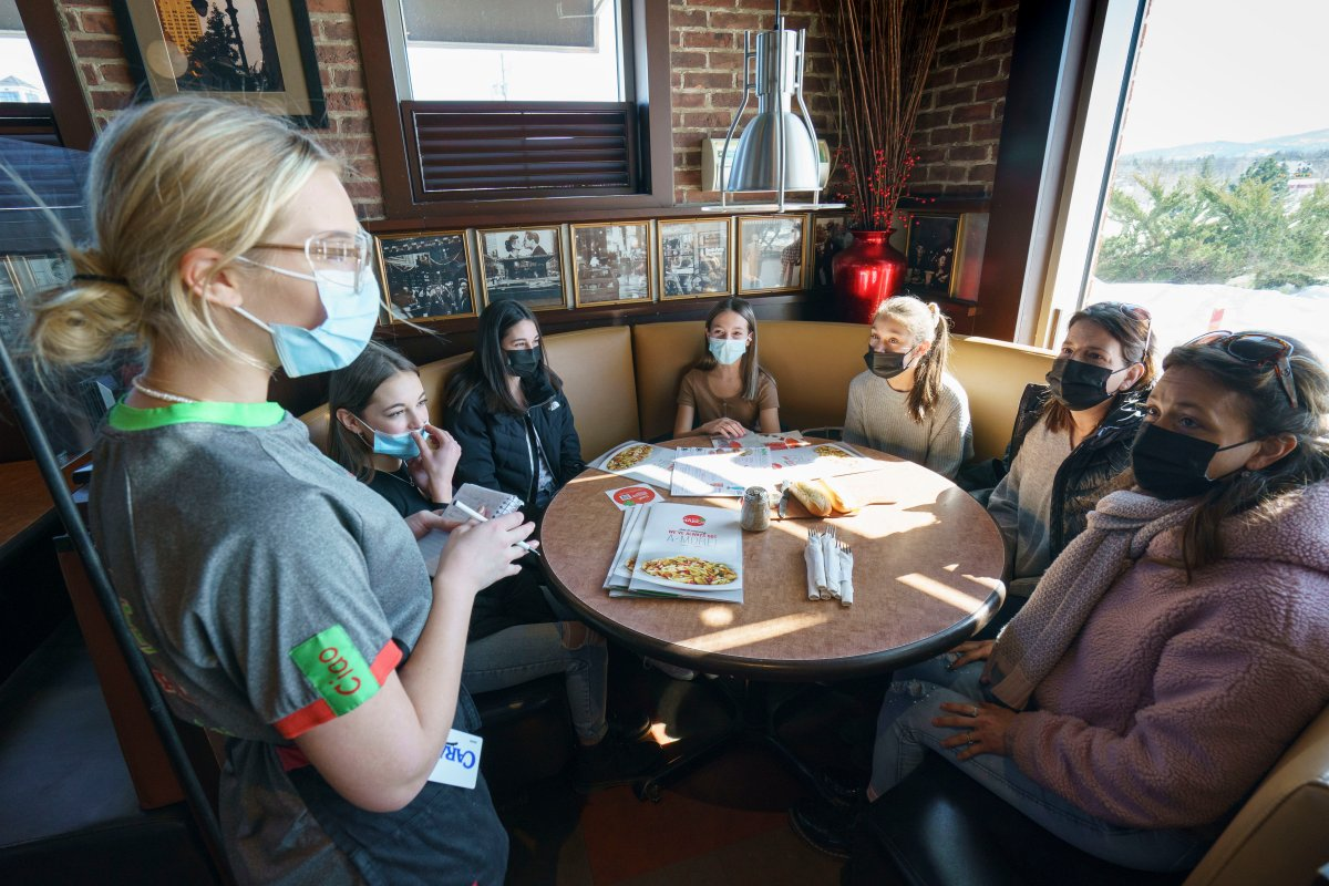 Waitress Myrtille Faucher takes customers' orders at the Eastside Mario's restaurant in Bromont, Que., on Monday, March 8, 2021. Customers are allowed to dine in as of Monday in restaurants outside of Greater Montreal.