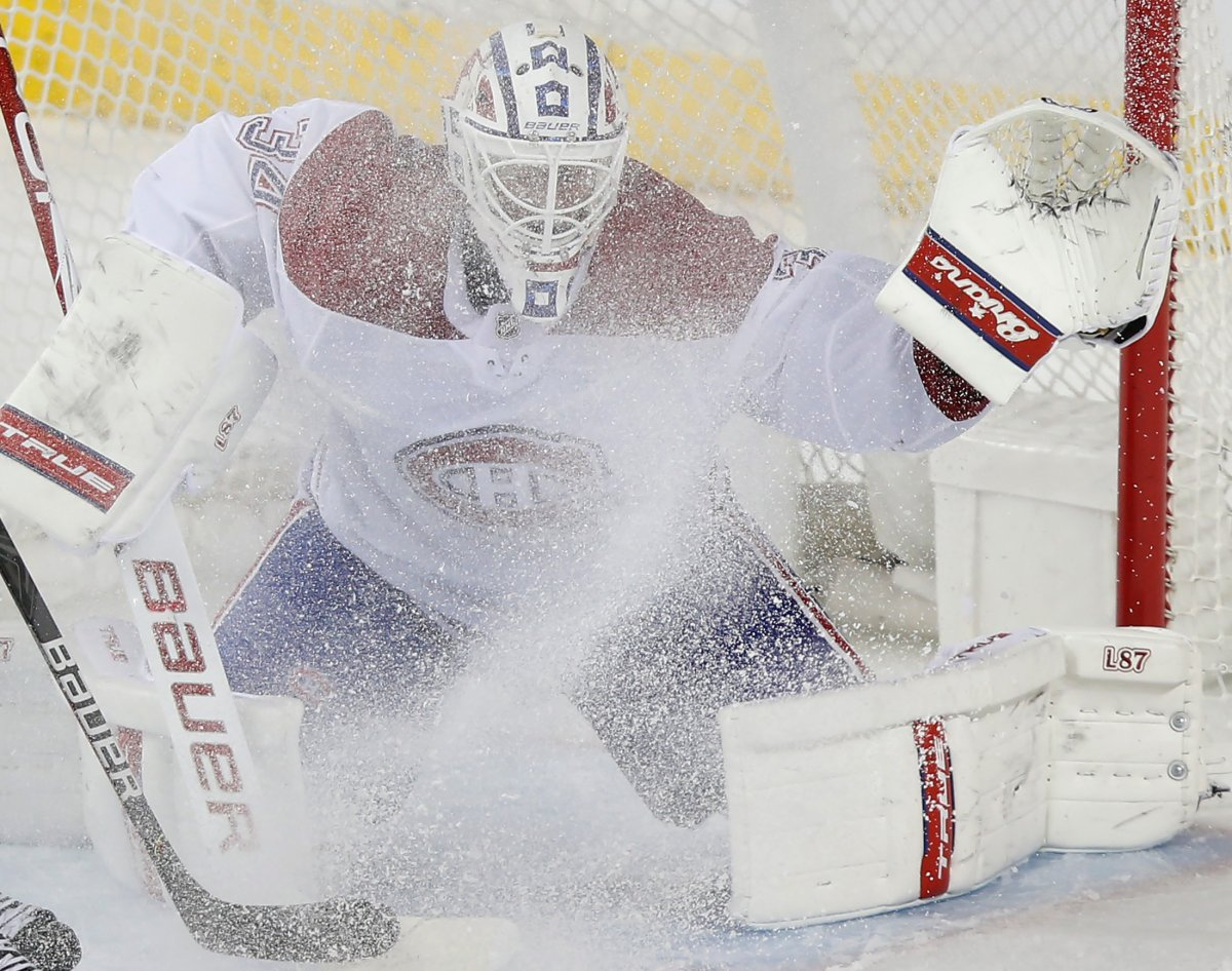 Montreal Canadiens goalie Jake Allen gets a face full of snow from Calgary Flames' Nikita Nesterov during the second period of their NHL hockey game in Calgary, Thursday, March 11, 2021.