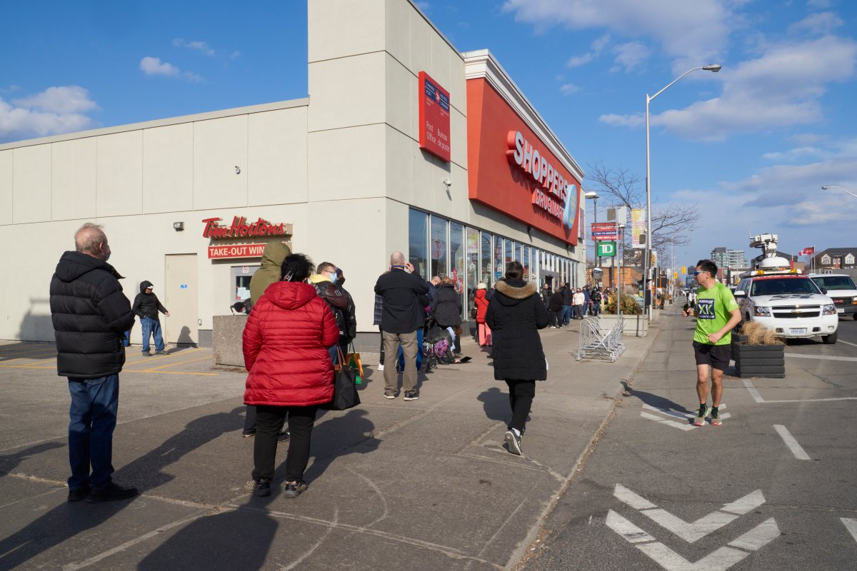 A man runs past people in the age group of 60-64 as they line up to get their Oxford-AstraZeneca COVID-19 vaccinations at the Shoppers Drug Mart at Danforth and Coxwell, in Toronto on March 11, 2021, exactly one year to the day that the World Health Organization declared a global pandemic.