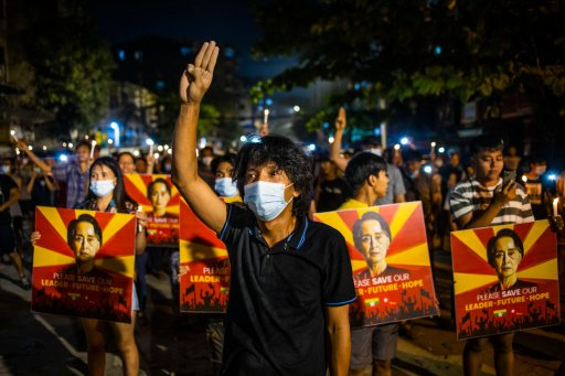 A man flashes the three-fingered gesture while others hold images of deposed Myanmar leader Aung San Suu Kyi during a candlelight night demonstration held out on the street despite a curfew imposed by authorities in Yangon, Myanmar on March 12, 2021.