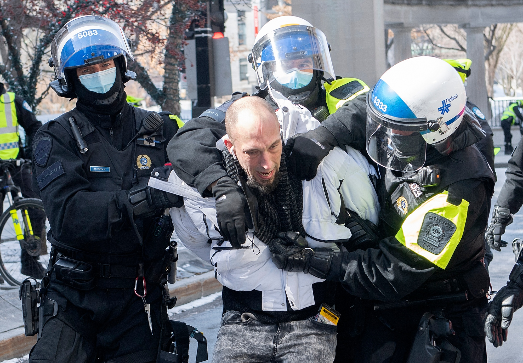 A man is detained by police during a demonstration to oppose government restrictions to curb the spread of Covid-19 in Montreal, Saturday, March 13, 2021.