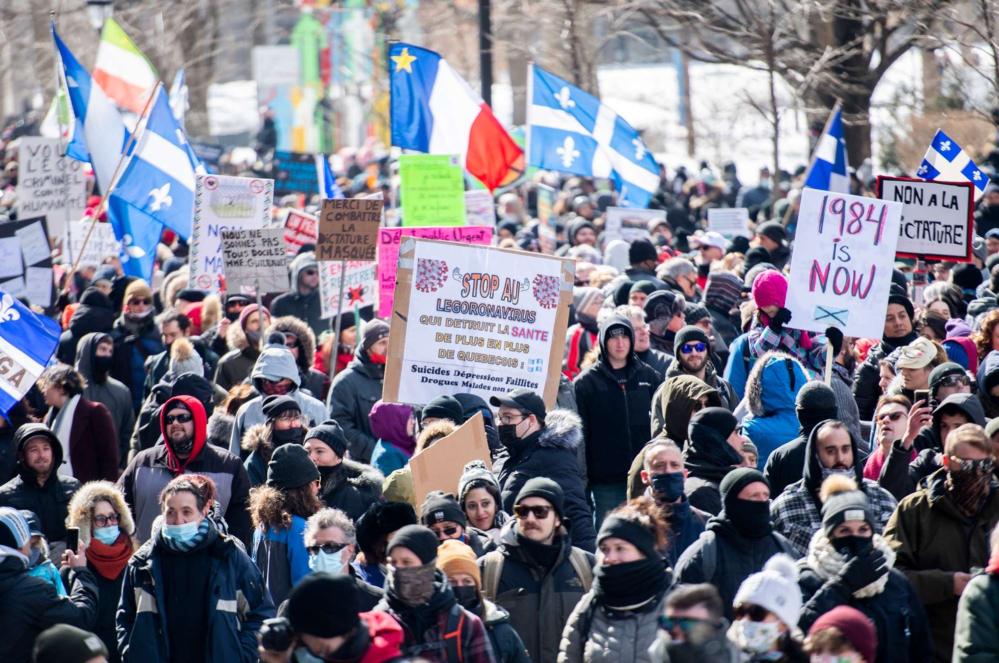 People take part in a demonstration to oppose government restrictions to curb the spread of Covid-19 in Montreal, Saturday, March 13, 2021.
