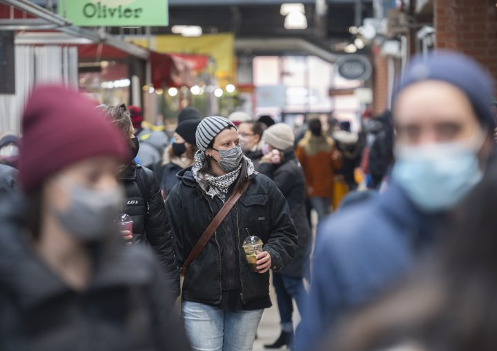 People wear face masks as they walk through a market in Montreal, Sunday, March 14, 2021, as the COVID-19 pandemic continues in Canada and around the world. THE CANADIAN PRESS/Graham Hughes