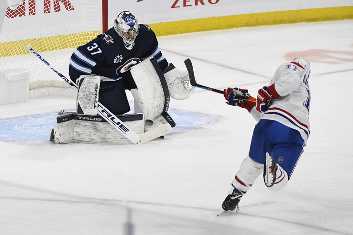 Winnipeg Jets goaltender Connor Hellebuyck (37) makes a save on a penalty shot by the Montreal Canadiens' Brendan Gallagher (11) during second-period NHL hockey action in Winnipeg, Monday, March 15, 2021.