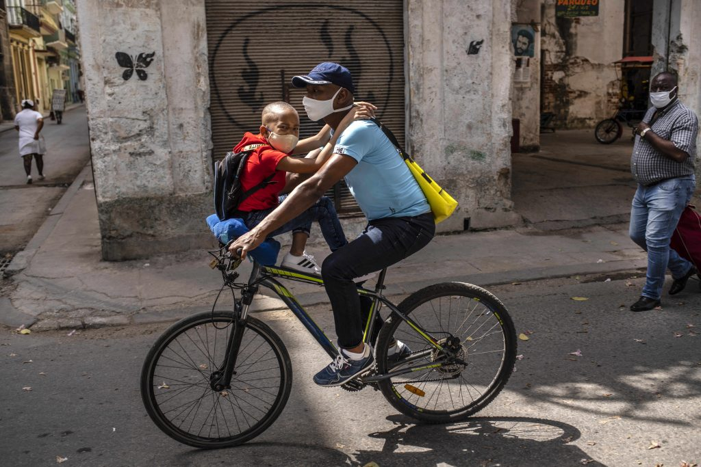 A man rides a bicycle with a child on his handlebars in Havana, Cuba, Friday, March 19, 2021, amid the COVID-19 pandemic. (AP Photo/Ramon Espinosa).