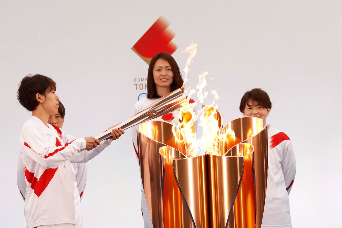 "The torch is lit by a member of Japan's women's national soccer team ""Nadeshiko Japan"" during the Tokyo 2020 Olympic Torch Relay Grand Start in Naraha, Fukushima prefecture, northeastern Japan, Thursday, March 25, 2021. The torch relay for the postponed Tokyo Olympics began its 121-day journey across Japan on Thursday and is headed toward the opening ceremony in Tokyo on July 23. (Kim Kyung-Hoon/Pool Photo via AP)."