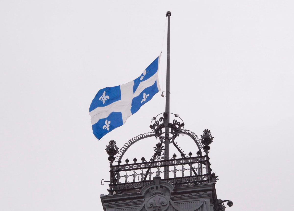 The Quebec flag flies at half-mast on the high tower of the national assembly.