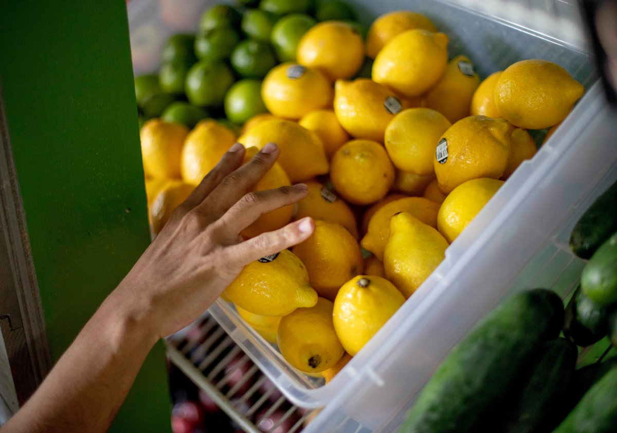 FILE - In this Aug. 21, 2019, file photo a worker stocks a produce stand at a metro station in Atlanta. Throwing away food is throwing away money. And with most wasted food winding up in landfills, it's not great for the environment, either.