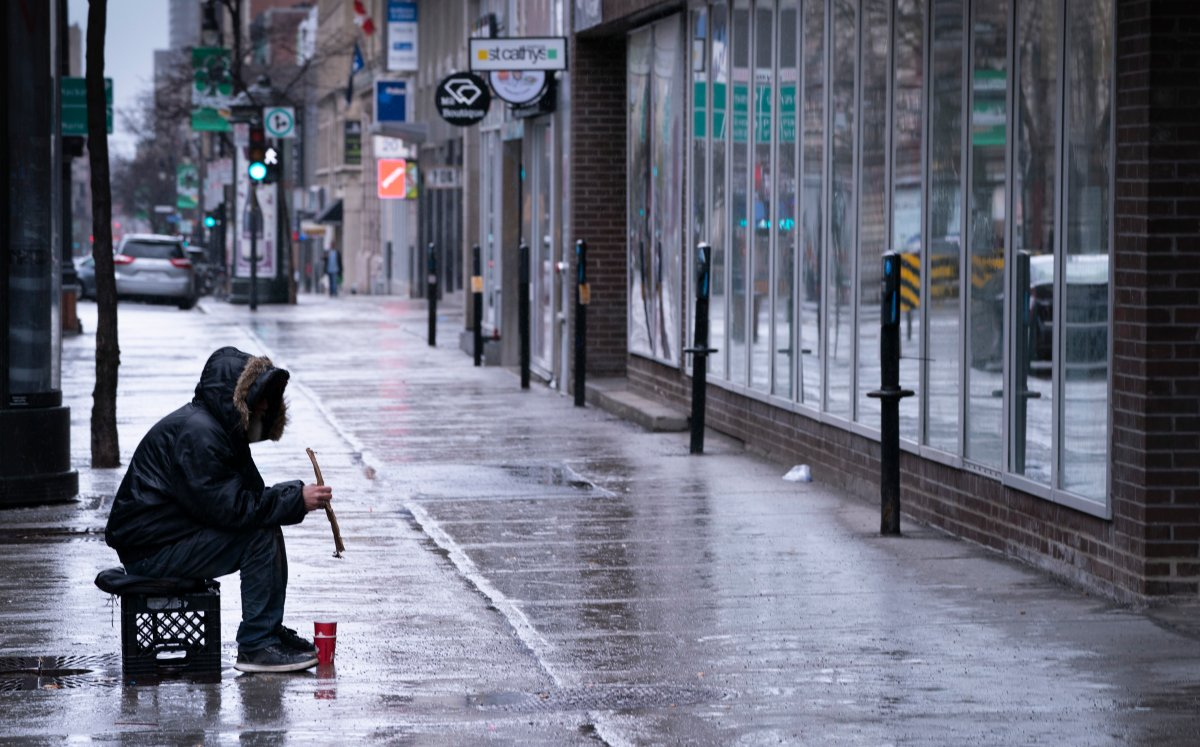 A homeless person sits alone on a sidewalk in downtown Montreal on Monday, March 30, 2020.