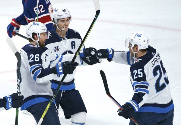 The Winnipeg Jets' Paul Stastny, right, celebrates his goal against the Montreal Canadiens with teammates Blake Wheeler, left, and Mark Scheifele during the first period in Montreal on Thursday.