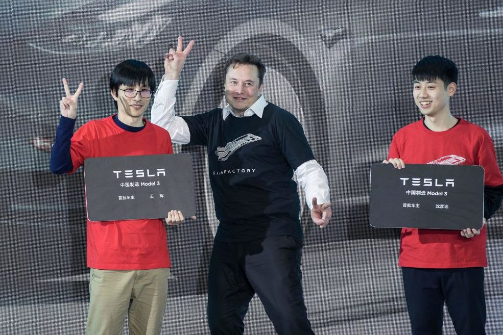 Tesla CEO Elon Musk poses with Tesla China-made Model 3 vehicle owners during a ceremony in Shanghai, east China, Jan. 7, 2020.
