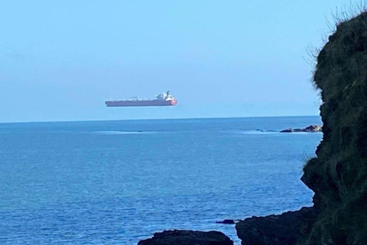 A tanker appears to hover above the water off the coast of Cornwall, England, in this photo captured by a pedestrian from shore.