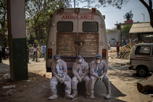 Exhausted workers, who bring dead bodies for cremation, sit on the rear step of an ambulance inside a crematorium, in New Delhi, India, Saturday, April 24, 2021. As India suffers a bigger, more infectious second wave with a caseload of more than 300,000 new cases a day, the country's healthcare workers are bearing the brunt of the disaster.