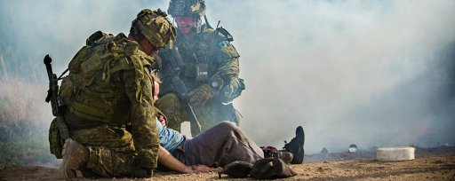 Members of the Royal 22e Régiment escort a civilian with simulated injuries to a secure area for medical treatment after accident scenario during Exercise Maple Resolve at CFB Wainwright, Alta. on 15 May 2018.