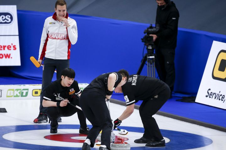 Team Canada skip Brendan Bottcher, left, looks on as South Korea skip Yeong Seok Jeong directs his teammates  at the Men's World Curling Championships in Calgary, Alta., Monday, April 5, 2021.