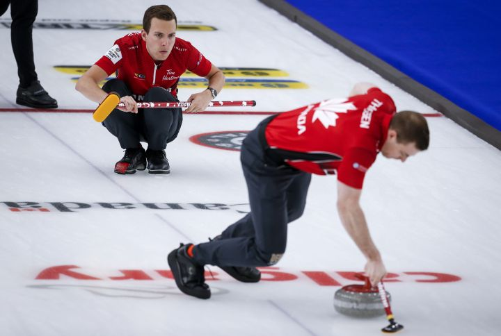 Team Canada skip Brendan Bottcher, left, makes a shot as second Brad Thiessen sweeps against Scotland in the qualification round at the Men's World Curling Championships in Calgary, Alta., Friday, April 9, 2021.
