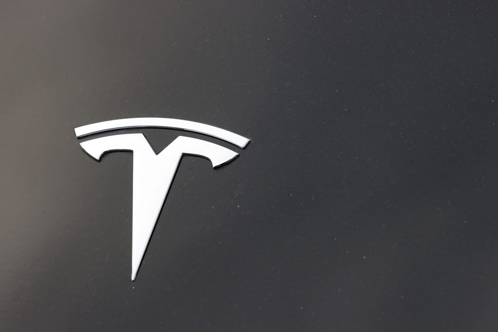The company logo is seen on the hood of an unsold Tesla at a dealership late Sunday, Aug. 9, 2020, in Littleton, Colo.  (AP Photo/David Zalubowski).
