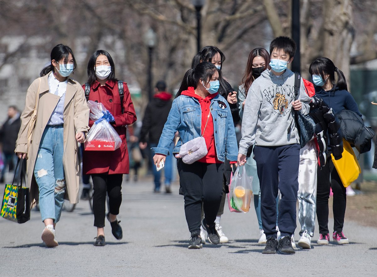 People wear face masks as they walk in a park in Montreal, Sunday, April 4, 2021, as the COVID-19 pandemic continues in Canada and around the world.