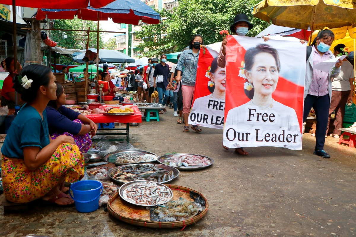 Anti-coup protesters walk through a market with images of ousted Myanmar leader Aung San Suu Kyi at Kamayut township in Yangon, Myanmar Thursday, April 8, 2021.