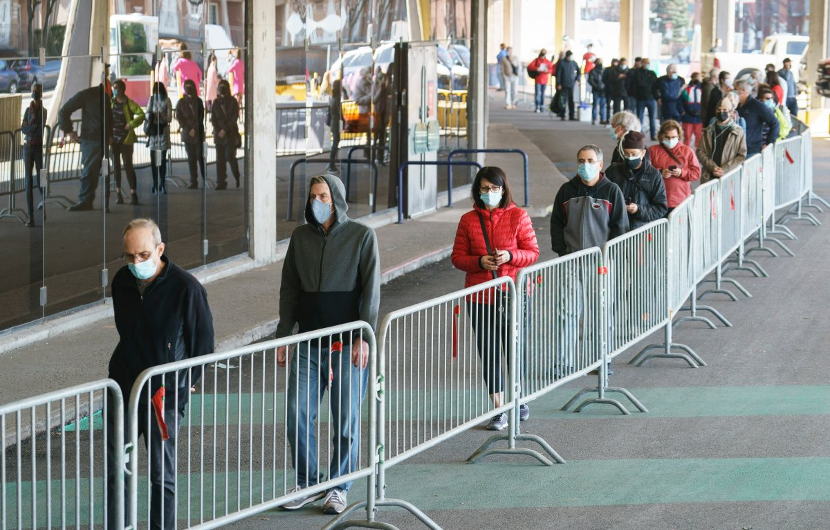 People wait in line at a COVID-19 vaccination clinic to receive the AstraZeneca vaccine at the Olympic Stadium in Montreal, on Thursday, April 8, 2021. Quebecers 55 and over can now get the AstraZeneca vaccine at walk-in clinics across the province.